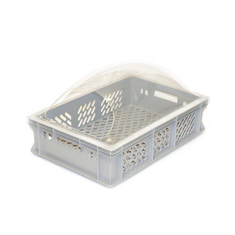 harmaa ritiläinen leipomolaatikko jonka yllä kirkas suojakupu jossa päädyssä aukko